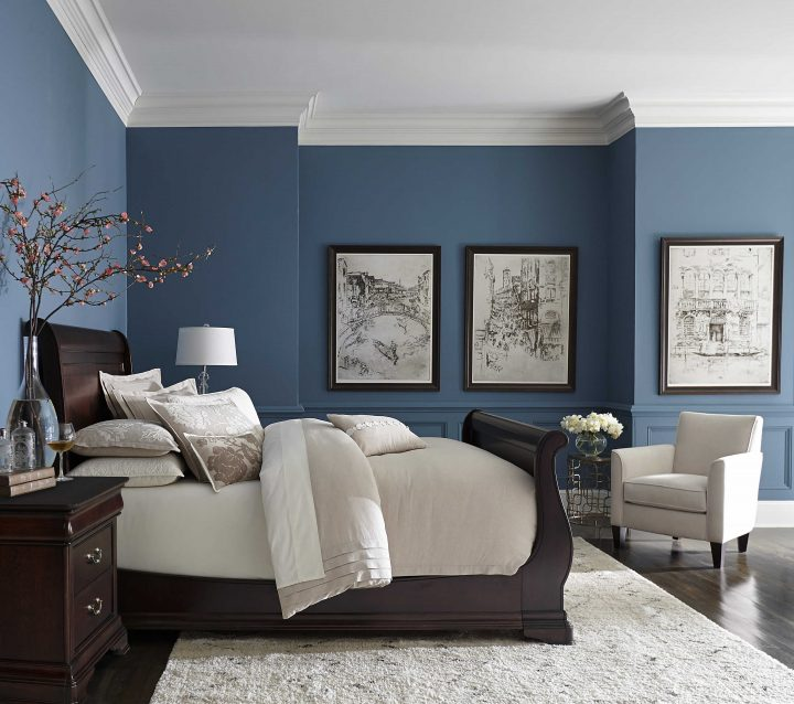 Bedroom Colour Scheme: Blue Walls Contrast with Cream Carpet, Furniture and Bed-Linen and the Dark Wood Bedframe, Nightstand, Floor, and Pictureframes