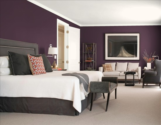 Bedroom Colour Scheme: Dark Purple Walls Contrast with Beige Carpet, Ceiling and Sofa; Grey Bedframe, Armchair and Bench at the End of the Bed Complete the Look