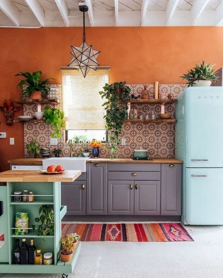 Bohemian Kitchen with Orange Wall, Light Blue Fridge, Mint Green Island and Plum Kitchen Unit as well as Reddish Sun-Patterned Tiles and Pink and Red Striped Carpet