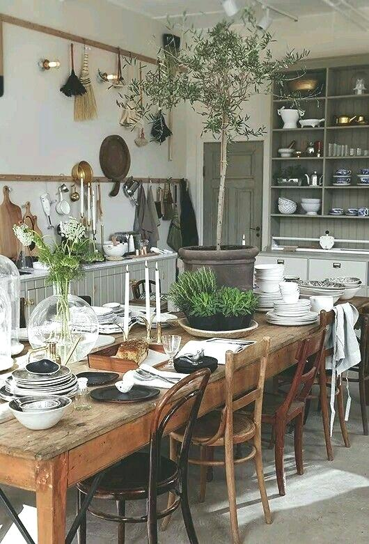 Massive Dining Table as Centrepiece of the Bohemian Kitchen - a Mixture of Mismatched Chairs, Stacks of Dinnerware, and even Potted Plants Riddle the Surface and Create an Inviting, Lived In Atmosphere