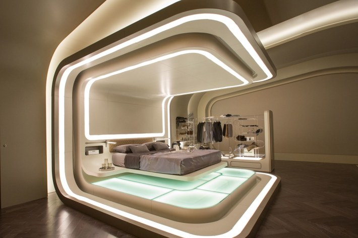 Futuristic Bedroom Idea: Floating Bed Inside a Pod-Like Construction With Lit Floor and Small, Open Clothesrack in the Background