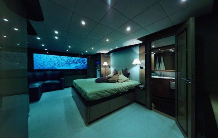 Futuristic Bedroom Idea: Bedroom Done Up in Blue and Green Hues with a Large Rectangular Screen on the Wall Showing Shoals of Fish