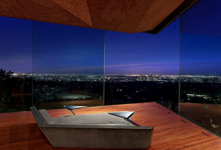 Futuristic Bedroom Idea: Modern Bed Shaped Like an Arrowhead Facing the Corner of Two Large Window Fronts Looking Out over the City Below