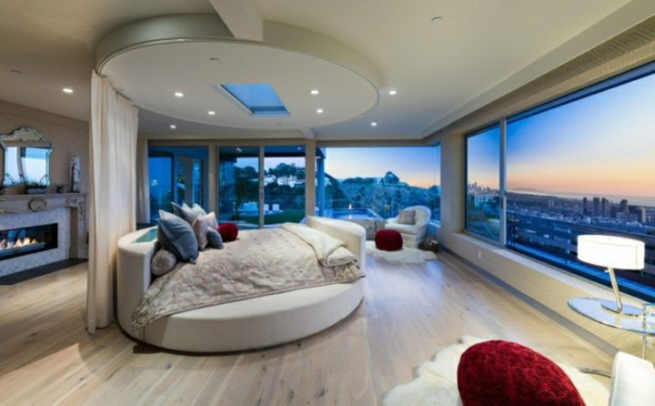 Futuristic Bedroom Idea: Circular Bed with Privacy Curtain Set in Front of a Large Window Front Overlooking the Skyline and the Sea in the Distance