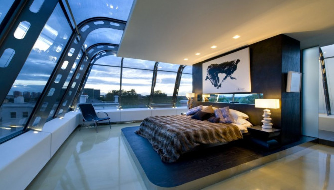 Futuristic Bedroom Idea: Bed on a Raised Platform With Dark Headboard Set in Front of a Large Window Front Separated With Industrial Iron Beams that Appear to Hold op the Glass Ceiling