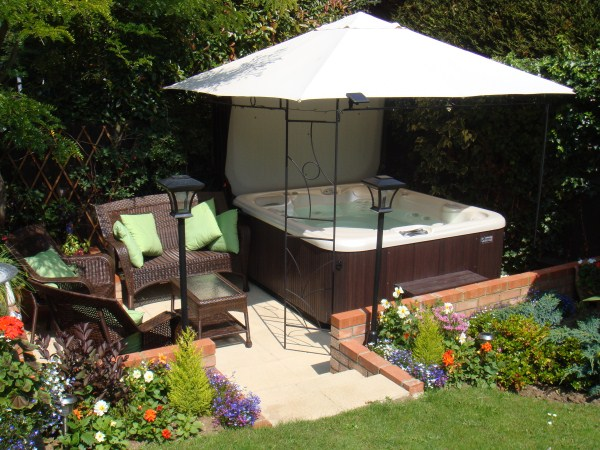 Hot Tub Under White Linen Roof Gazebo Tucked into a Small Garden