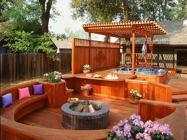 Hot Tub with Slatted Gazebo Set Slightly Above a Lower Level Seating Area With Fire Pit