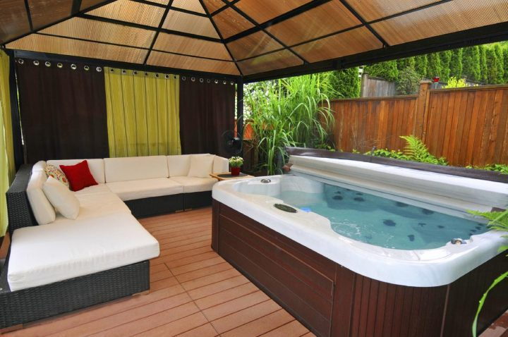 Hot Tub Located Under a Pavilion Alongside a Comfy Sectional Sofa
