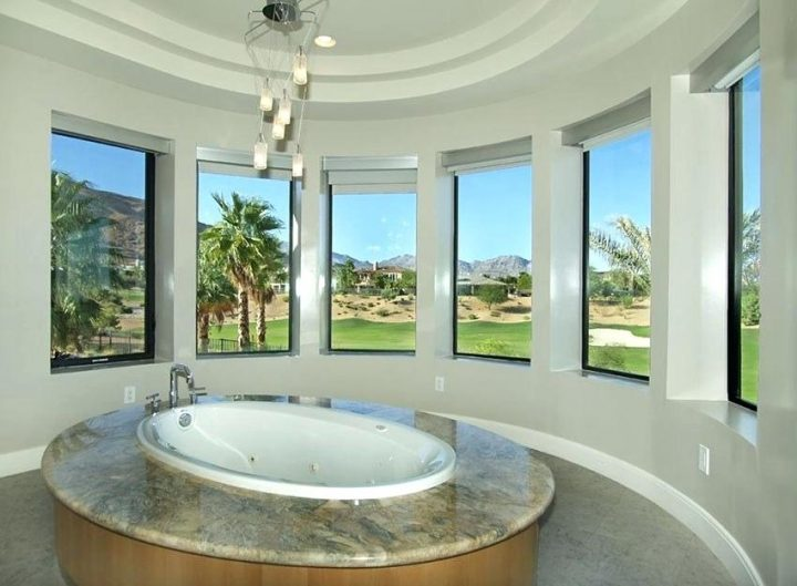 Modern Oval Master Bathroom With View and Equally Oval Sunken Tub And Modern Chandelier Atop