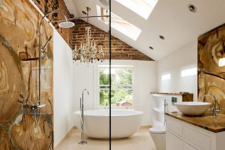 Masterbathroom with Extravagant Stone Lining Behind Shower and Sink and a Beautiful Traditional Chandelier Hanging Over the Free-Standing Tub