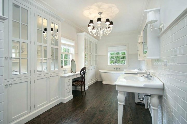 Master Bathroom in White with Dark Brown Wood Floor and Chandelier With Dark Lamp Shades
