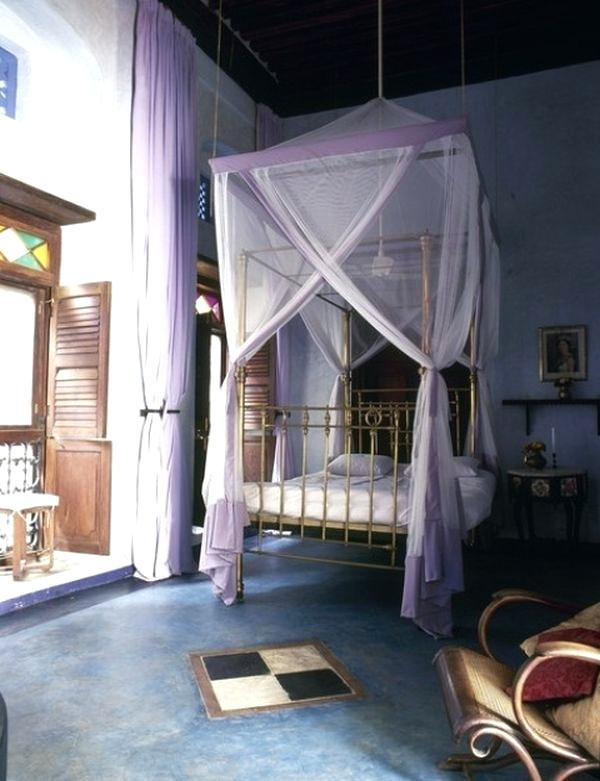 Moroccan Bedroom Decor: Lavender Coloured Sheer Fabric Draped Over Four-Poster Frame
