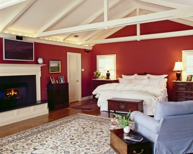 Red Bedroom With White Bed, Fireplace, and Light Blue Armchair